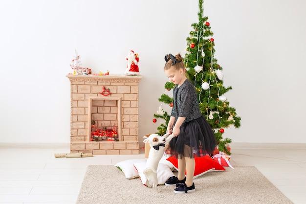 Menina brincando com o cachorrinho jack russell terrier perto da árvore de natal