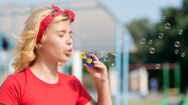 Menina brincando com o ventilador de bolha ao ar livre
