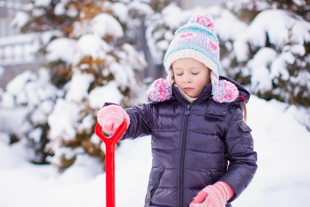 Menina brincando com pá vermelha no jardim no dia de inverno
