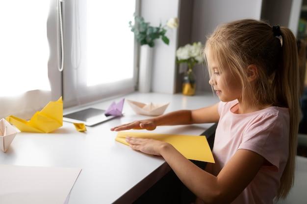 Menina brincando com papel de origami em casa