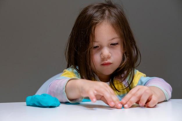 Menina brincando com plastilina (massinha) em fundo cinza.