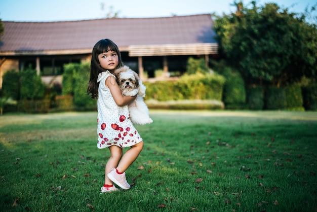 Menina brincando com seu cachorrinho no parque de verão