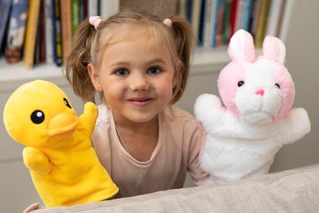 Menina brincando com seus fantoches em casa