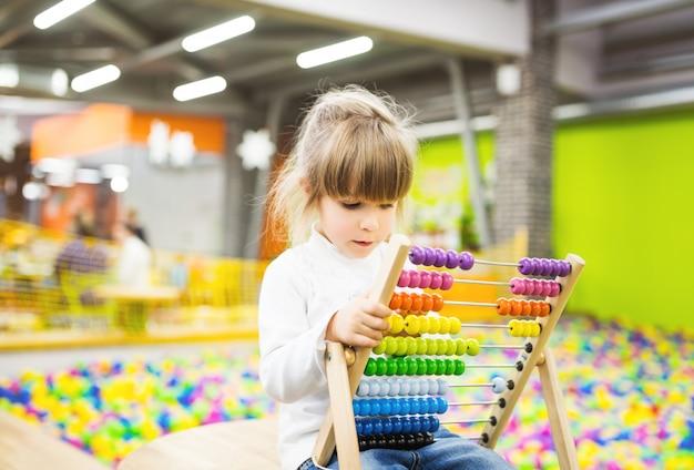 Menina brincando com um brinquedo de madeira de ábaco