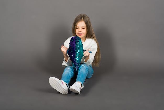 Menina brincando com um brinquedo de tubarão amarelo