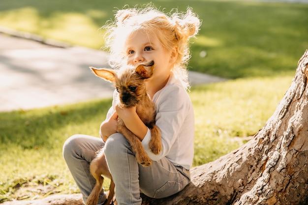 Menina brincando com um cachorrinho ao ar livre