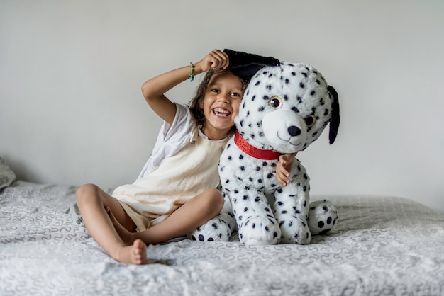 Menina brincando com um cachorro de pelúcia