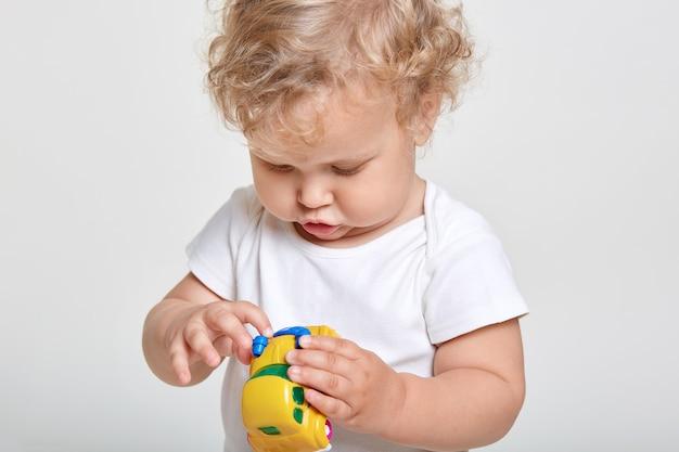 Menina brincando com um carro amarelo, olhando para o carro de brinquedo com grande interesse, vestindo camiseta