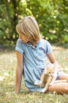 Menina brincando com um gatinho ao ar livre no parque