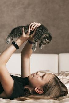 Menina brincando com um gatinho britânico
