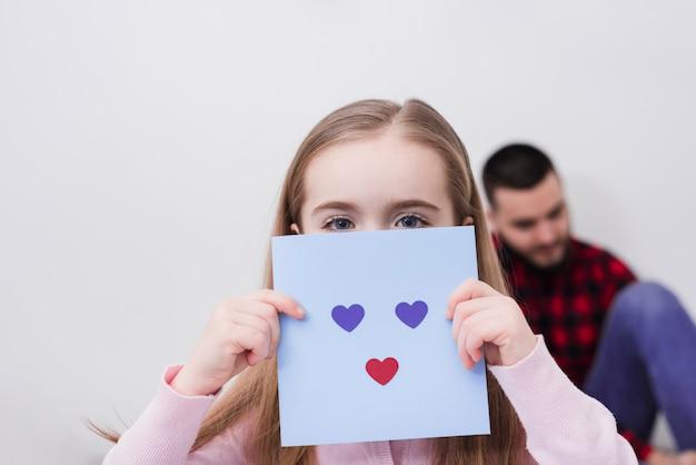 Menina brincando com um rosto feito de corações