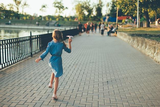 Menina brincando, correndo com o avião de papel de brinquedo