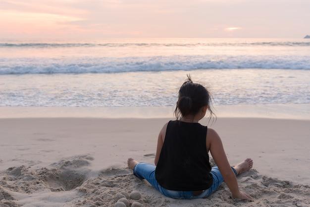 Menina brincando de areia na praia