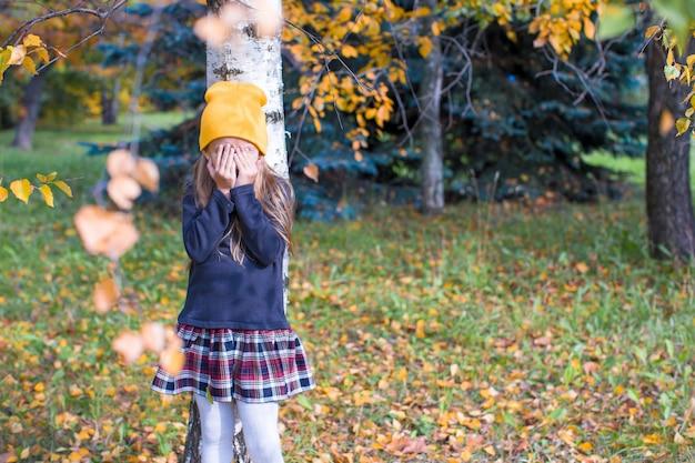 Menina brincando de esconde-esconde na floresta de outono