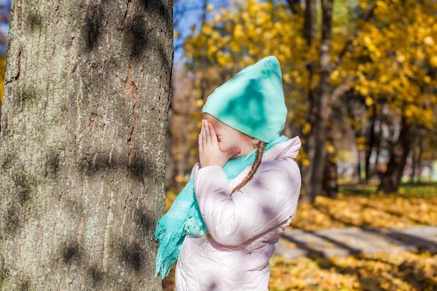 Menina brincando de esconde-esconde perto da árvore na floresta de outono