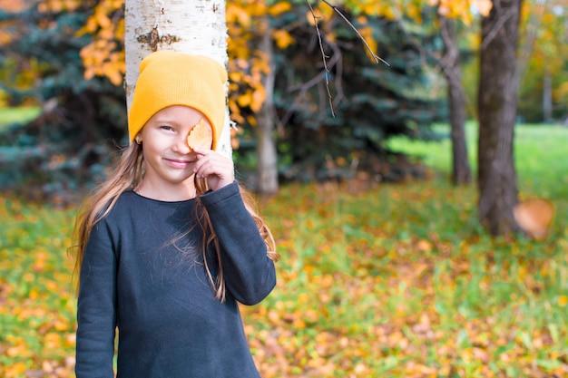 Menina brincando de esconde-esconde perto de árvore no parque outono