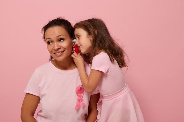 Menina brincando de médico com a mãe dela. linda mulher afro-americana com a menina-de-rosa com fita rosa, símbolo do dia internacional de conscientização do câncer de mama. conceito médico educacional