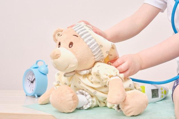 Menina brincando de médico e ouvindo ursinho de pelúcia com estetoscópio despertador e comprimidos no fundo