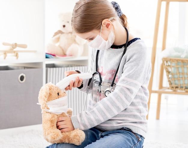 Menina brincando durante a quarentena, médico com ursinho de pelúcia