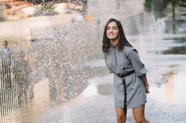 Menina brincando e dançando em uma rua molhada