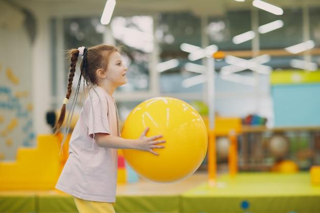 Menina brincando e fazendo exercícios com uma grande bola amarela no ginásio do jardim de infância ou escola primária.
