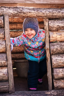 Menina brincando em uma casa de madeira