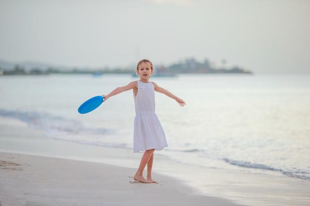 Menina brincando em uma praia tropical branca