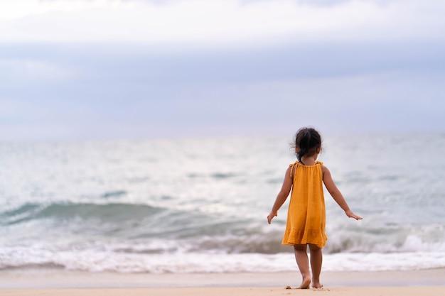 Menina brincando na beira-mar ao entardecer.