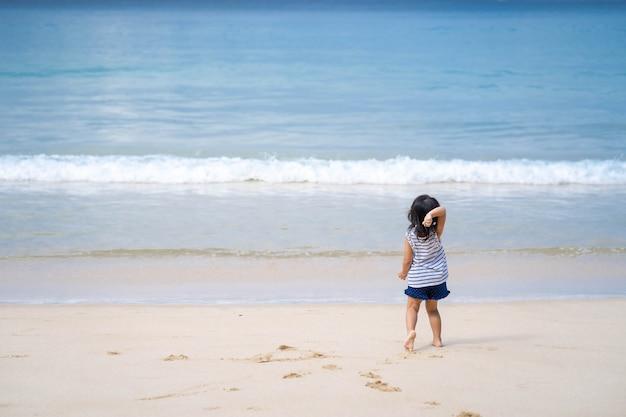 Menina brincando na bela costa do mar.