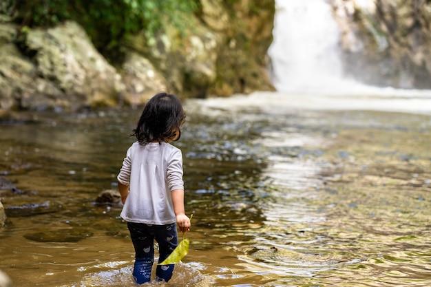 Menina brincando na cachoeira durante as férias de verão Foto Premium