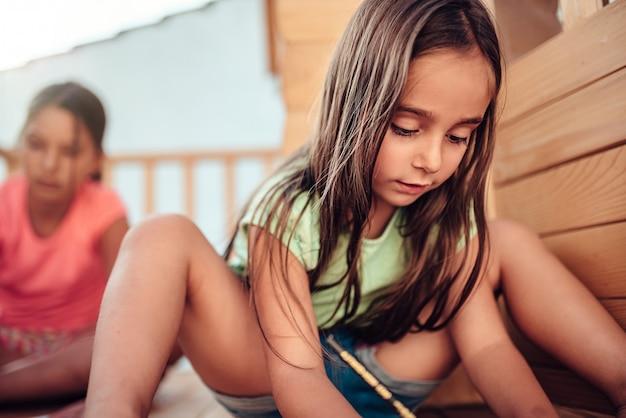 Menina brincando na casa da árvore com os amigos e desenhar com lápis de cor