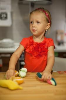 Menina brincando na cozinha com frutas e legumes