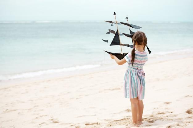 Menina brincando na praia com pipa de navio
