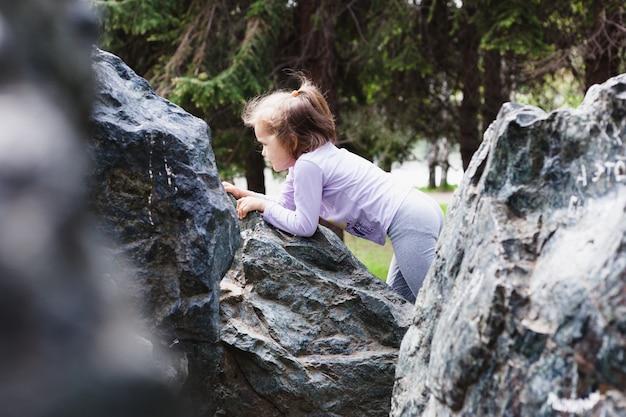 Menina brincando nas rochas, escalada, infância e alegria, brincando com outras crianças, desenvolvimento