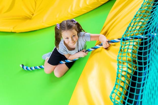 Menina brincando no centro de trampolim pulando e subindo com corda