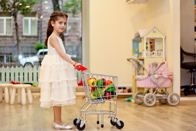 Menina brincando no jardim de infância. segurando a cesta do supermercado com frutas artificiais