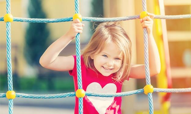 Menina brincando no parquinho no parque da cidade