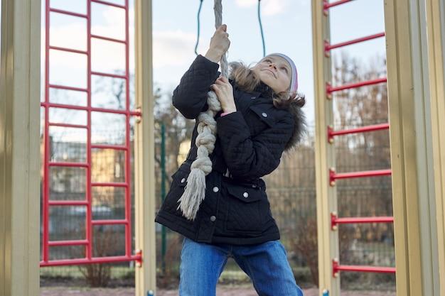Menina brincando no parquinho, segurando corda