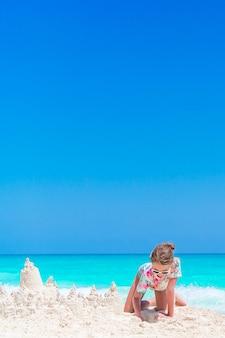 Menina brincar com brinquedos de praia durante as férias tropicais