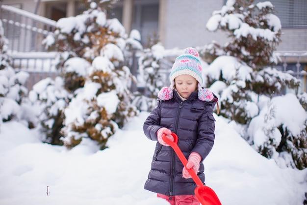 Menina brincar com neve pá em um dia de inverno