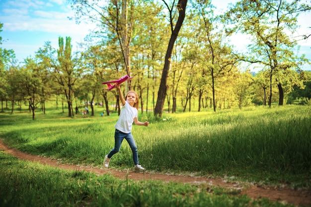 Menina, brincar com um avião de brinquedo no ar no parque. criança lança um avião de brinquedo. menina bonita, corra na grama e lança um avião de brinquedo rosa