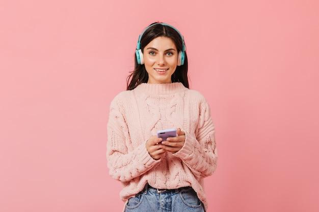 Menina bronzeada de cabelos escuros com sorriso encantador olha para a câmera. lady em fones de ouvido muda a música no telefone.