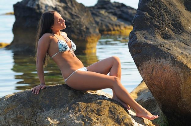 Menina bronzeada em traje de banho, sorrindo e posando deitada de costas em uma rocha à beira-mar