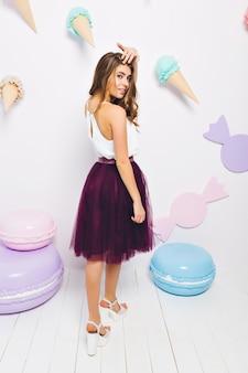 Menina bronzeada magro com saia violeta longa olhando por cima do ombro, posando na festa temática e tocando o cabelo. retrato de corpo inteiro de uma linda jovem em pé na sala de luz decorada com doces.