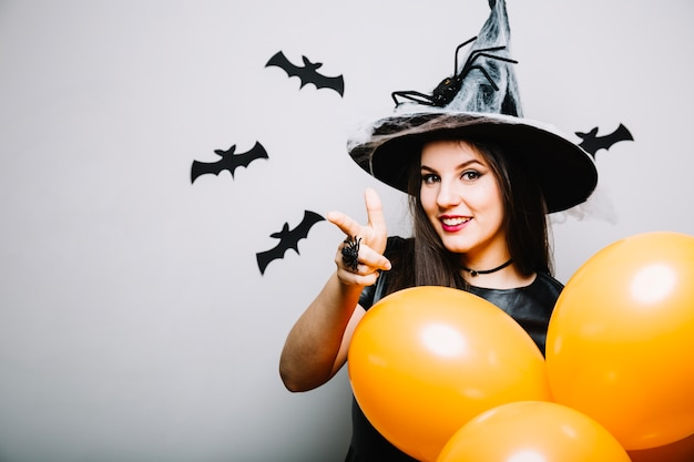 Menina bruxa apontando para longe