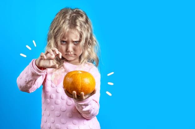 Menina bruxa bonito com cabelo loiro evoca uma abóbora no azul