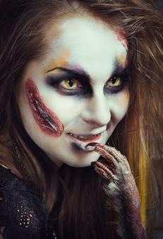 Menina bruxa zumbi come o pássaro antes do halloween. bruxa está se preparando para as noites de férias dos mortos