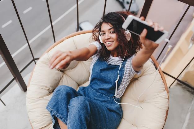 Menina cacheada animada com vestido jeans deitada em um travesseiro grande e macio e curtindo música pela manhã