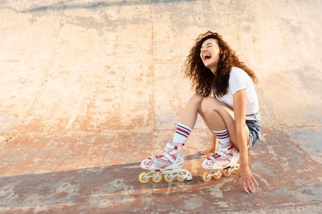 Menina cacheada posando em patins com espaço de cópia