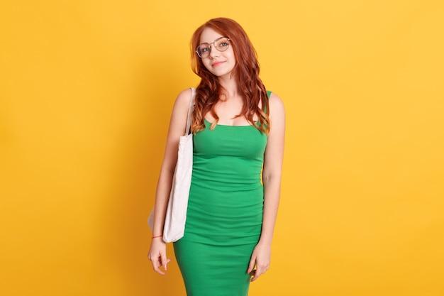 Menina calma com aparência agradável posando contra uma parede amarela com espaço de cópia para anúncio ou texto promocional